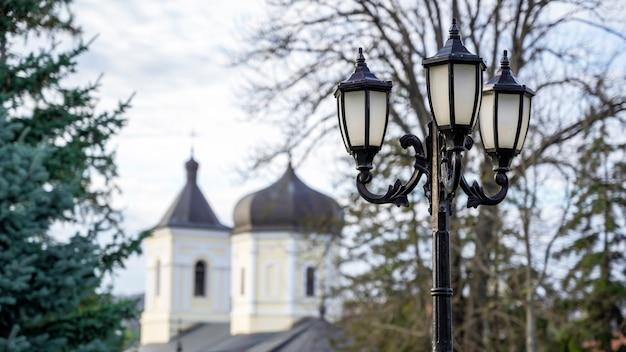 Lampadaire vintage avec l'église en pierre et les arbres. monastère de capriana, moldavie