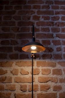 Lampadaire vintage en métal sur fond de mur de brique rouge
