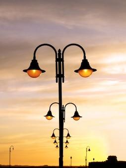Les lampadaires ornementaux allumés à l'aube sont alignés verticalement.