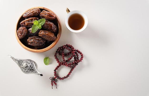Lampe aladdin fruits dates et chapelet sur fond gris