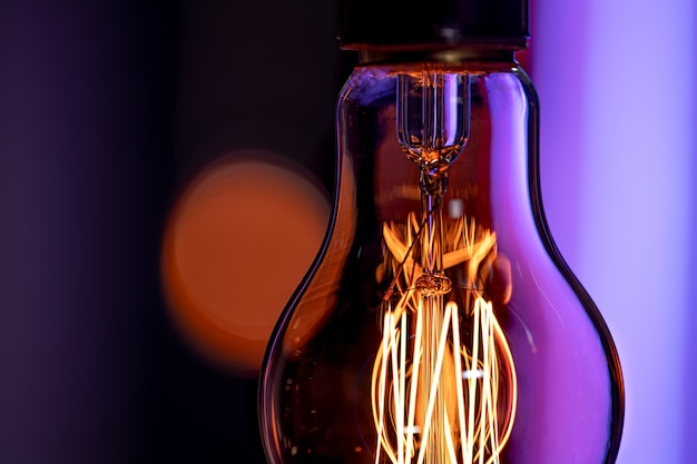Une lampe allumée est suspendue dans l'obscurité sur un arrière-plan flou. le concept de décor et d'ambiance.