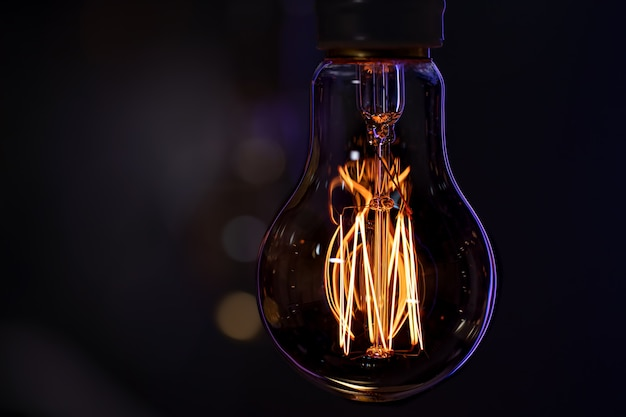 Une lampe allumée est suspendue dans l'obscurité. le concept de décor et d'ambiance.