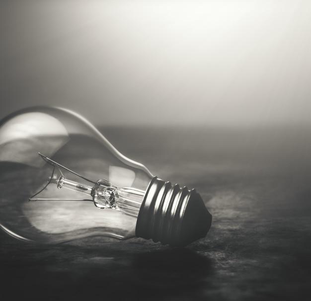 Lampe ampoule de ton sombre sur le concept de fond dramatique de plancher.