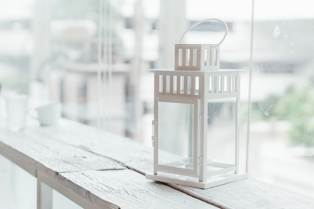 Lampe ancienne blanche sur une table en bois peinte en blanc avec fenêtre en verre et arbres en arrière-plan.