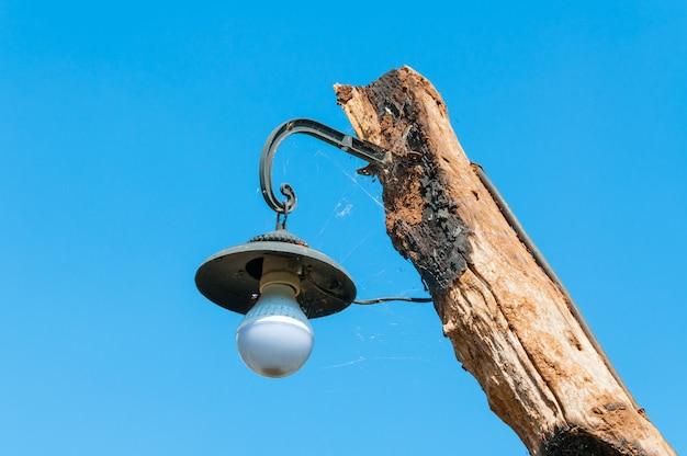 Lampe ancienne sur poteau en bois sur bluesky