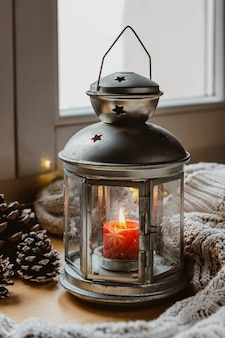 Lampe à angle élevé avec bougie, pommes de pin et couverture