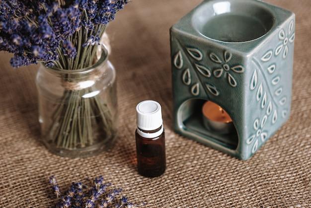 Lampe aromatique avec une bougie allumée et de l'huile essentielle, fond avec espace copie