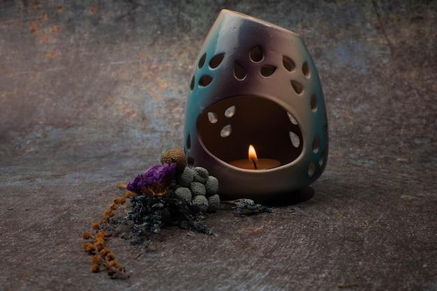 Lampe aromatique avec une bougie dans la pénombre sur fond bleu. photo de haute qualité