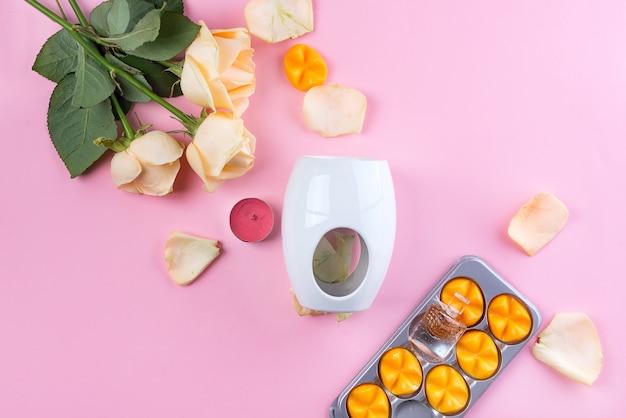 Lampe aromatique à la cire essentielle et aux roses jaunes sur fond rose
