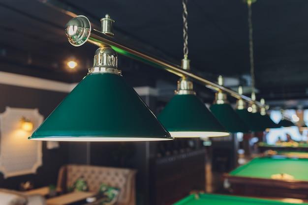Lampe sur billard vert boules de table et queues.