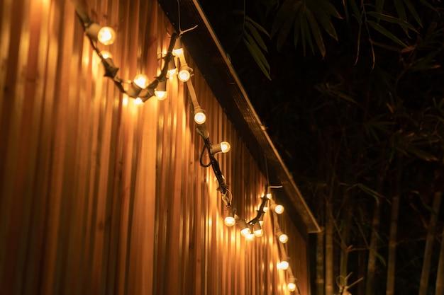 La lampe à boule de tungstène dans la ligne est accrochée à une cloison de lattes de bois la nuit en plein air avec un fond de bambou.