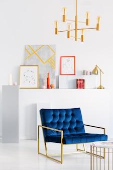 Lampe dorée au-dessus du fauteuil bleu à l'intérieur du salon blanc avec galerie d'affiches. vrai photo