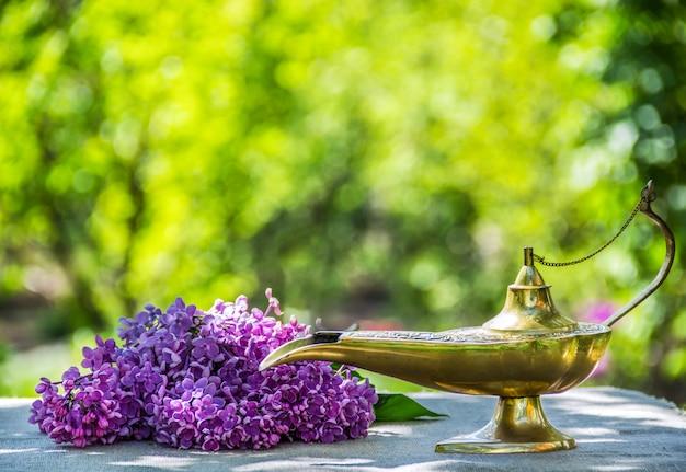 Lampe à huile et fleurs lilas dans le jardin