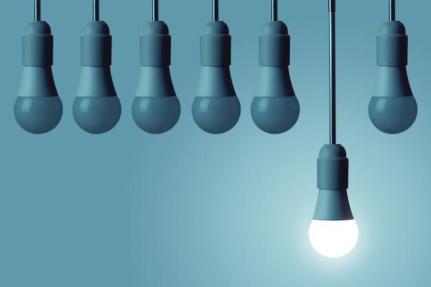 La lampe led est allumée et les autres ampoules ne brillent pas sur un fond bleu profond. concept de créativité.
