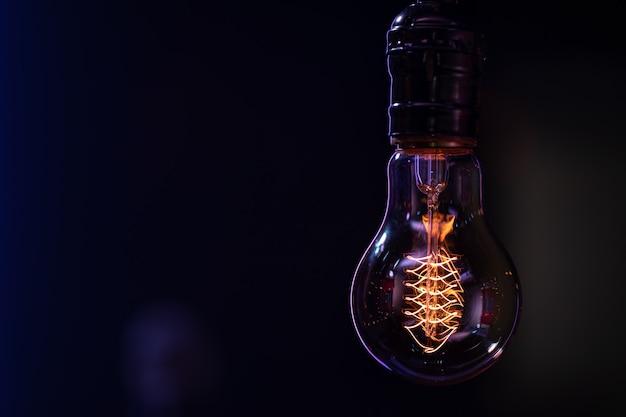 Une lampe lumineuse est suspendue dans l'espace de copie d'arrière-plan flou sombre.
