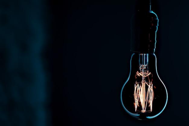 Lampe lumineuse suspendue dans l'obscurité. concept de décor et d'ambiance.