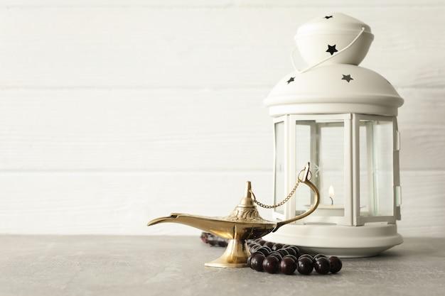 Lampe magique avec des perles de prière et une lanterne du ramadan sur une table grise sur fond de bois