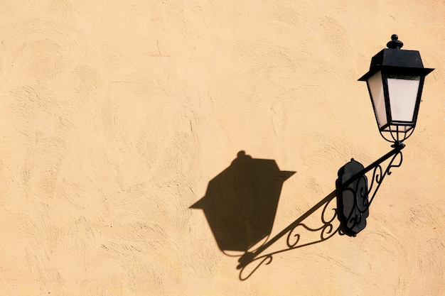 Lampe en métal décorative de style vintage sur un vieux mur de béton avec l'ombre de la lumière dure de la lumière du soleil avec espace de copie.