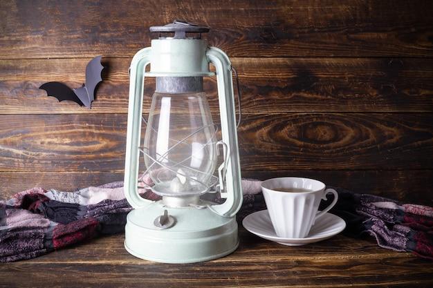 Lampe à pétrole rougeoyante et tasse de thé sur une surface de planche de bois marron avec une chauve-souris en papier et un tissu hétéroclite