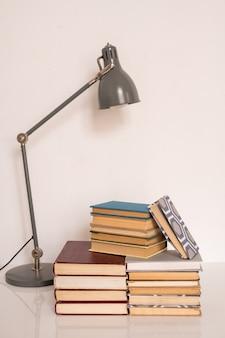 Lampe sur des piles de livres et de manuels sur la table ou le lieu de travail de l'étudiant du collège ou de l'école contre un mur blanc en studio