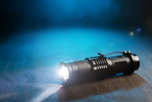 Lampe de poche étanche tactique. la lampe de poche led brille sur la table en fumée.