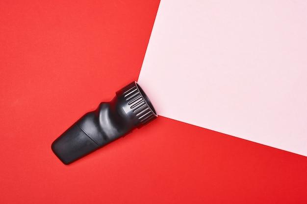 Lampe de poche sur fond rouge avec un rayon de lumière rose, fabriqué à partir de l'espace de copie papier