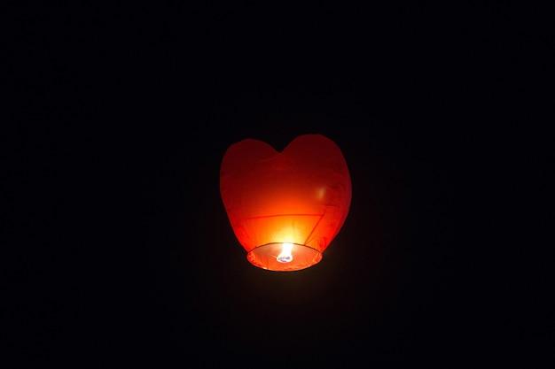 Lampe de poche en forme de coeur rouge chinoise vole dans le ciel nocturne. joyeux anniversaire été et mariage. isolé sur fond noir