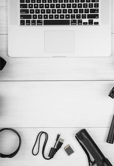 Lampe de poche noire; câble usb et carte mémoire avec ordinateur portable sur un bureau en bois blanc