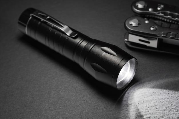 Lampe de poche noire sur la surface de la pierre. outils pour le travail, la recherche et le tourisme ..