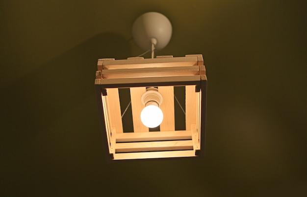 Lampe à poser en bois suspendue au plafond.