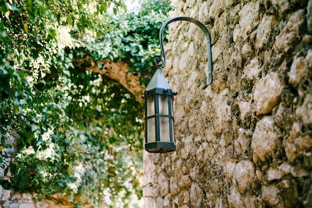 Lampe de rue près des arbres sur un mur de pierre dans la vieille ville de bar au monténégro.