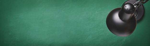 Lampe de table noire sur plateau vert. concept de retour à l'école. maquette pour la conception. espace de copie. concept d'éducation. bannière.