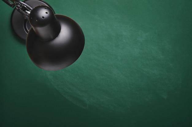 Lampe de table noire sur plateau vert. concept de retour à l'école. maquette pour la conception. espace de copie. concept d'éducation.