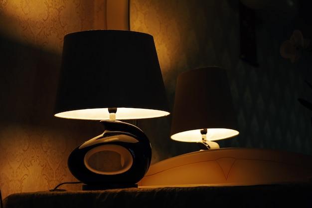 Lampe sur une table de nuit à côté d'un lit