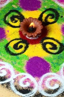Lampes en argile diya allumées pendant la célébration de diwali, rangoli en arrière-plan