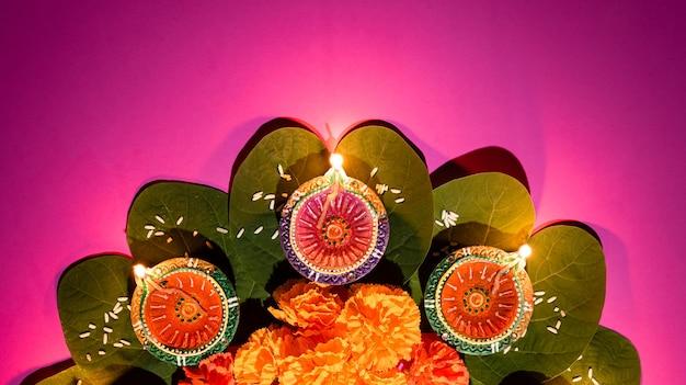 Lampes en argile diya allumées pendant dussehra avec fleurs jaunes, feuilles vertes et riz