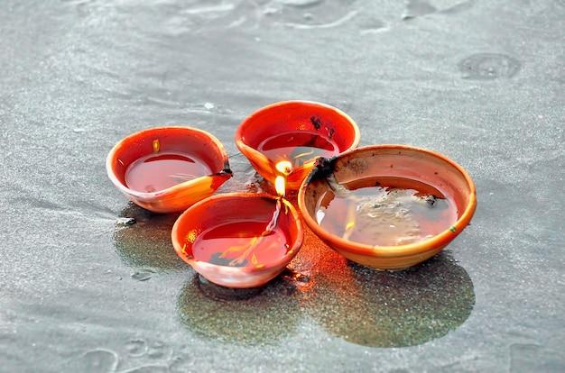 Lampes et bougies traditionnelles de diwali allumées sur la plage de sable. mise au point sélective, dof peu profond et bruit visible dû à une faible luminosité.
