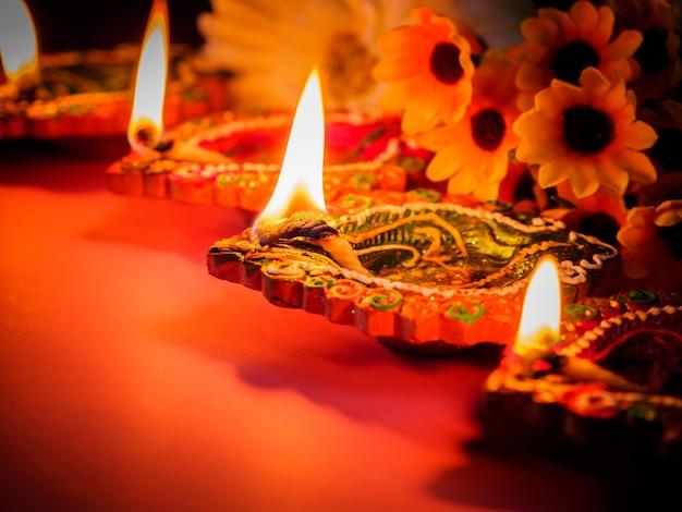 Lampes diya en argile colorées illuminées de fleurs pour le festival hindou diwali