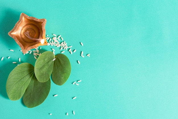 Lampes diya en terre cuite allumées pendant dussehra avec feuille verte et riz sur vert