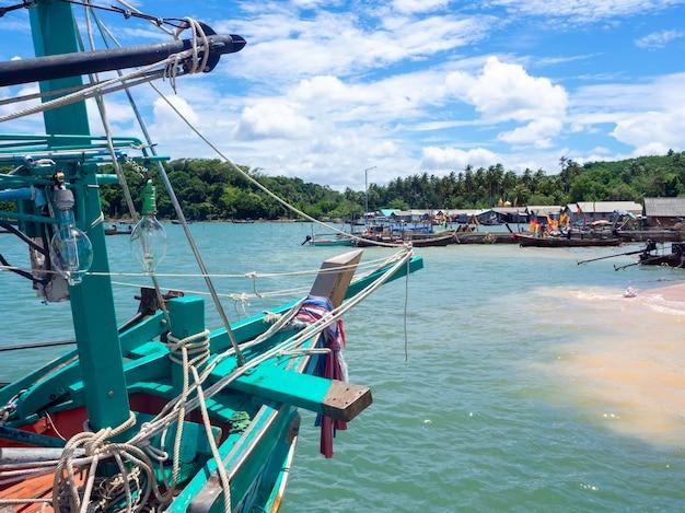 Des lampes lumineuses et de nombreuses cordes en désordre sur un bateau de pêcheur local en bois sur le quai se bouchent