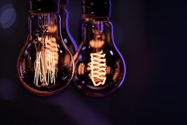 Des lampes lumineuses pendent dans l'obscurité du boke. concept de décor et d'ambiance.