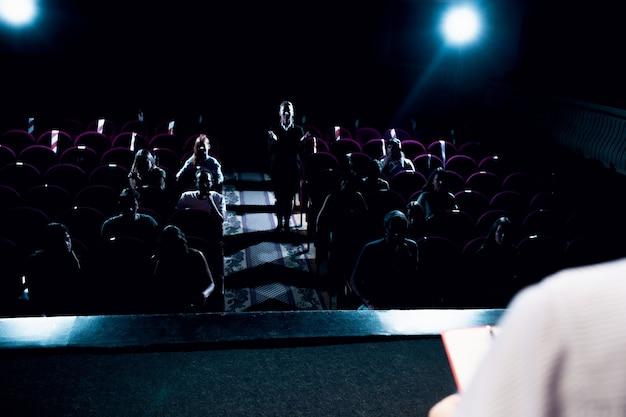 Lampes de poche de salle. orateur masculin faisant une présentation dans le hall de l'atelier. centre d'affaires. vue arrière des participants en public. conférence événement, formation. éducation, réunion, concept d'entreprise.