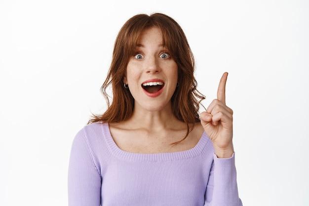 Lancer une idée. une jeune femme excitée a une suggestion, haletant étonné, levant le doigt, pointant vers le haut et disant un plan, a une solution intéressante, debout sur blanc