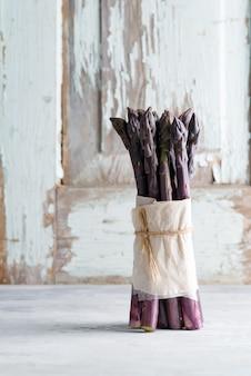 Lances asperges violettes organiques crues prêtes à cuire des aliments diététiques sains sur un fond de pierre clair.