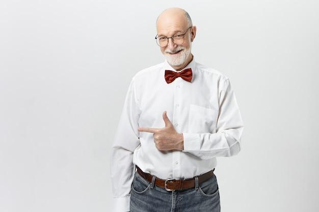 Le langage du corps. heureux homme âgé positif en jeans décontractés, lunettes, chemise et nœud papillon rouge souriant, pointant l'index loin, indiquant un mur de fond vierge pour votre contenu publicitaire