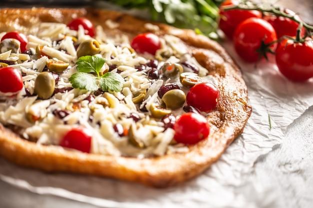 Langos savoureux et croustillants parfaitement servis avec des tomates cerises entières, du fromage râpé, des haricots et des olives vertes grecques.