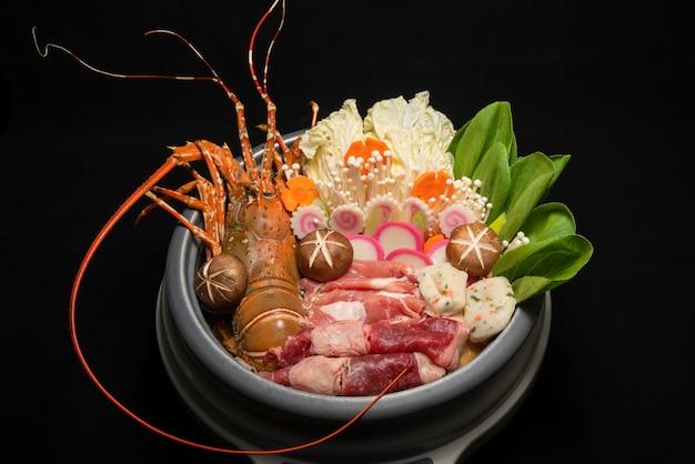 Langouste servie dans un plat chaud avec légumes et viande soupe de homard nabe shabu