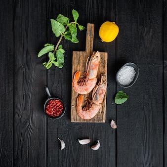 Langoustines aux fruits de mer sur planche de bois sur table en bois noir