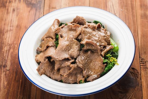 La langue de boeuf bouilli avec des légumes est servie sur une assiette dans un restaurant