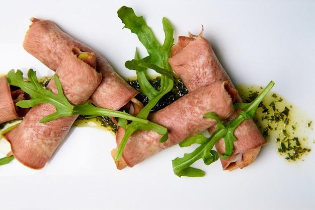 Langue cuite avec garniture et sauce sur un plat blanc.